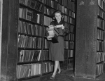 Woman collecting books in a library