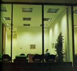 A man sits alone in his office. He is speaking on the telephone.