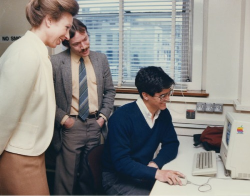 Three people around an old computer. One of them is Princess Anne. It is the eighties.