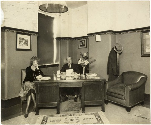 Man and woman sat at a desk. It is the 1920s. They don't look too happy.