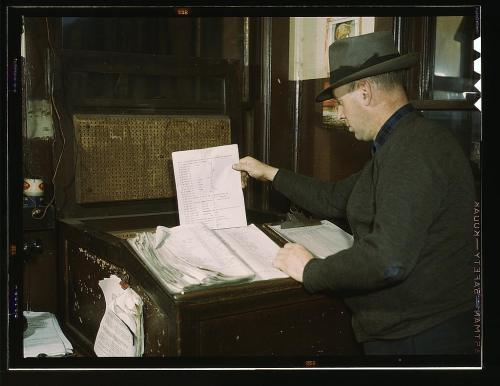 Man checking over lists. He is wearing a great hat.