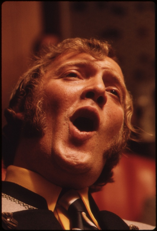 Man singing in the 1970s. He has wonderful sideburns.