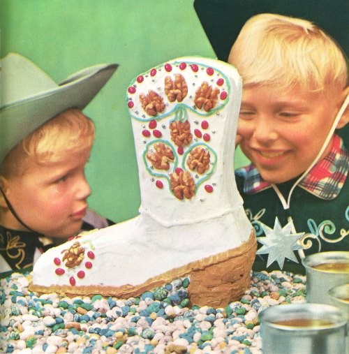 Boys dressed as cowboys look at awesome cowboy boot cake