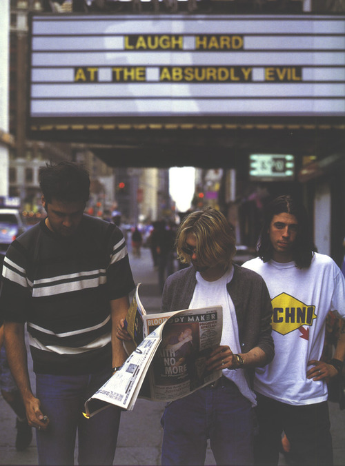 Nirvana standing outside a cinema reading Melody Maker