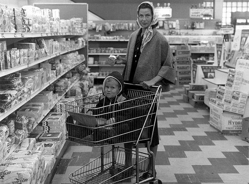 Woman in supermarket, child in trolley