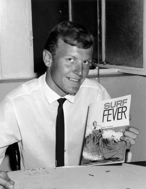 Man holding up 'Surf Fever' book