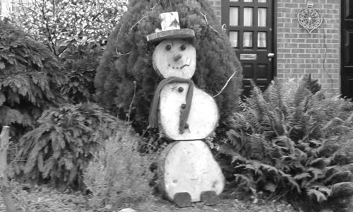 Snowman made of wood, outside house