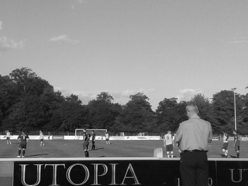 "Man watching football by ""Utopia"" sign"