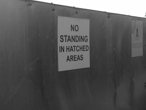 No standing in hatched areas sign